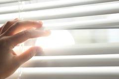 Donna che apre i ciechi di finestra orizzontali a casa Spazio per testo immagini stock