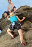 Donna che arrampica in su la corda della stretta dell'uomo della roccia Immagini Stock