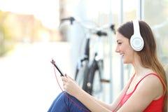 Donna che ascolta la musica da una compressa in un parco Fotografie Stock