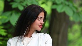 Donna che ascolta la musica da uno Smart Phone con le cuffie in un parco, bella donna che per mezzo dello smartphone con le cuffi video d archivio