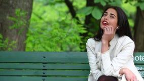 Donna che ascolta la musica da uno Smart Phone con le cuffie in un parco, bella donna che per mezzo dello smartphone con le cuffi archivi video