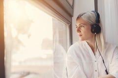 Donna che ascolta la musica, guardante attraverso la finestra fotografia stock libera da diritti