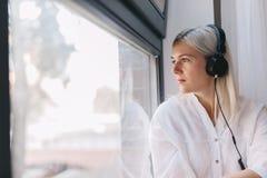Donna che ascolta la musica, guardante attraverso la finestra fotografia stock