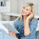 Donna che ascolta la musica sulla sua compressa Fotografie Stock Libere da Diritti