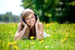 Donna che ascolta la musica sulle cuffie o Fotografia Stock Libera da Diritti