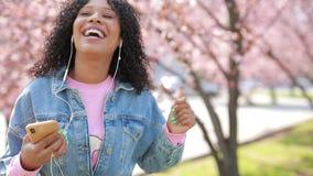 Donna che ascolta la musica in un parco, albero dei fiori di ciliegia intorno