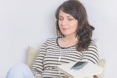 Donna che ascolta un audiolibro fotografia stock libera da diritti