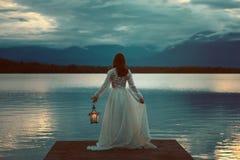 Donna che aspetta con la lanterna su un pilastro immagini stock libere da diritti