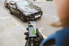 Donna che aspetta l'automobile del uber sullo smartphone della tenuta della via fotografie stock
