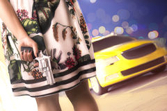 Donna che aspetta un taxi giallo con la pistola nascosta Fotografia Stock