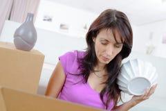 Donna che assicura gli oggetti fragili in scatola prima del muoversi Fotografie Stock