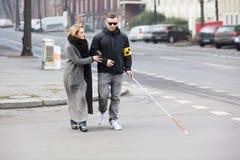 Donna che assiste uomo cieco sulla via fotografia stock libera da diritti