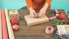 Donna che avvolge il contenitore di regalo con la decorazione degli oggetti sulla tavola di legno, fine su, vista superiore archivi video