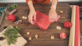 Donna che avvolge il contenitore di regalo con la decorazione degli oggetti sulla tavola di legno, fine su, vista superiore stock footage