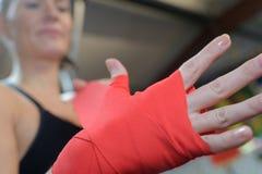 Donna che avvolge le mani con gli involucri rossi della mano di pugilato immagine stock