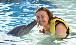 Donna che bacia delfino in stagno immagini stock libere da diritti