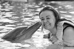 Donna che bacia delfino in stagno fotografie stock