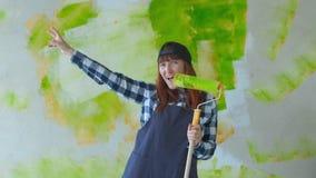 Donna che balla e che canta tenendo il rullo di pittura video d archivio