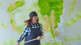 Donna che balla e che canta tenendo il rullo di pittura stock footage