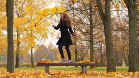 Donna che balla nel parco di autunno negli alberi di acero gialli luminosi video d archivio