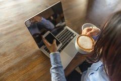 Donna che beve caffè caldo, Internet praticante il surfing sullo smartphone fotografia stock