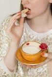 Donna che beve da una bella tazza arancio fatta a mano Immagine Stock