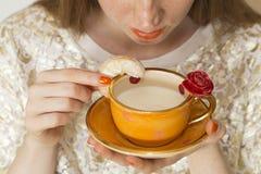 Donna che beve da una bella tazza arancio fatta a mano Fotografie Stock Libere da Diritti
