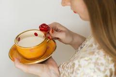 Donna che beve da una bella tazza arancio fatta a mano Fotografia Stock