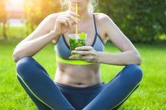 Donna che beve dopo l'allenamento corrente di forma fisica il giorno di estate Immagine Stock Libera da Diritti