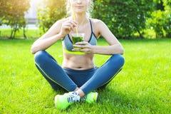 Donna che beve dopo l'allenamento corrente di forma fisica il giorno di estate Fotografia Stock