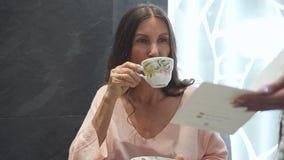 Donna che beve la sua bevanda nel centro della località di soggiorno di stazione termale video d archivio