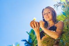 Donna che beve un cocktail della noce di cocco immagini stock libere da diritti