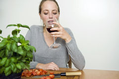 Donna che beve vino rosso mentre cucinando Immagine Stock Libera da Diritti