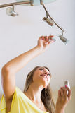 Donna che cambia le lampadine Fotografia Stock Libera da Diritti