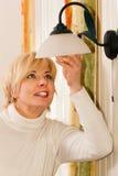 Donna che cambia una lampadina Fotografie Stock Libere da Diritti