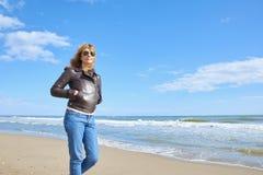 Donna che cammina alla spiaggia Immagini Stock
