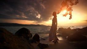 Donna che cammina alla spiaggia e che guarda all'orizzonte stock footage