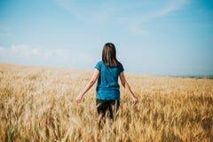 Donna che cammina attraverso il giacimento di grano, colpo del carrello Orecchie commoventi del grano della mano del ` s della ra Immagine Stock Libera da Diritti