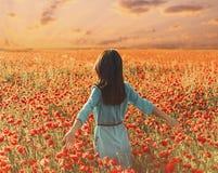 Donna che cammina attraverso il prato del papavero e che tocca i fiori fotografie stock