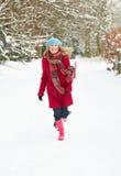 Donna che cammina attraverso il terreno boscoso dello Snowy Immagine Stock Libera da Diritti
