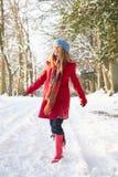 Donna che cammina attraverso il terreno boscoso dello Snowy Fotografia Stock