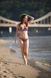 Donna che cammina attraverso la spiaggia del fiume Fotografia Stock