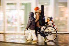 Donna che cammina con un bambino spingendo una bicicletta Fotografia Stock