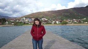 Donna che cammina da solo sul pilastro di legno con il rivestimento rosso Ragazza felice nella vacanza in un lago nelle montagne  stock footage
