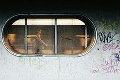 Donna che cammina dietro la finestra sulla stazione della metropolitana fotografia stock libera da diritti