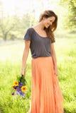 Donna che cammina in fiori di trasporto del campo di estate Fotografie Stock