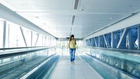 Donna che cammina fra i passaggi pedonali automatici, nell'incrocio del sottopassaggio, facendo uso del suo telefono, un mezzo di archivi video