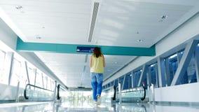 Donna che cammina fra i passaggi pedonali automatici, nell'incrocio del sottopassaggio, parlante, facendo uso del suo telefono, u archivi video