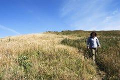 Donna che cammina giù una collina Immagine Stock Libera da Diritti
