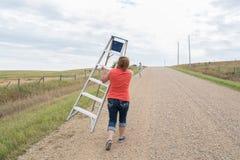 Donna che cammina giù una strada rurale con una scala a libretto fotografie stock libere da diritti